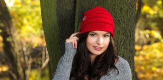 Smiling brunette Beauty during autumn wearing red beannie hat