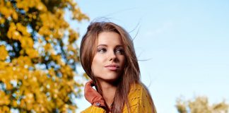 woman wearing mustard yellow sweater and marron red pants posing outdoors in fall autumn