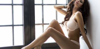 Sensual attractive brunette woman posing over the window wearing sexy lingerie looking at camera