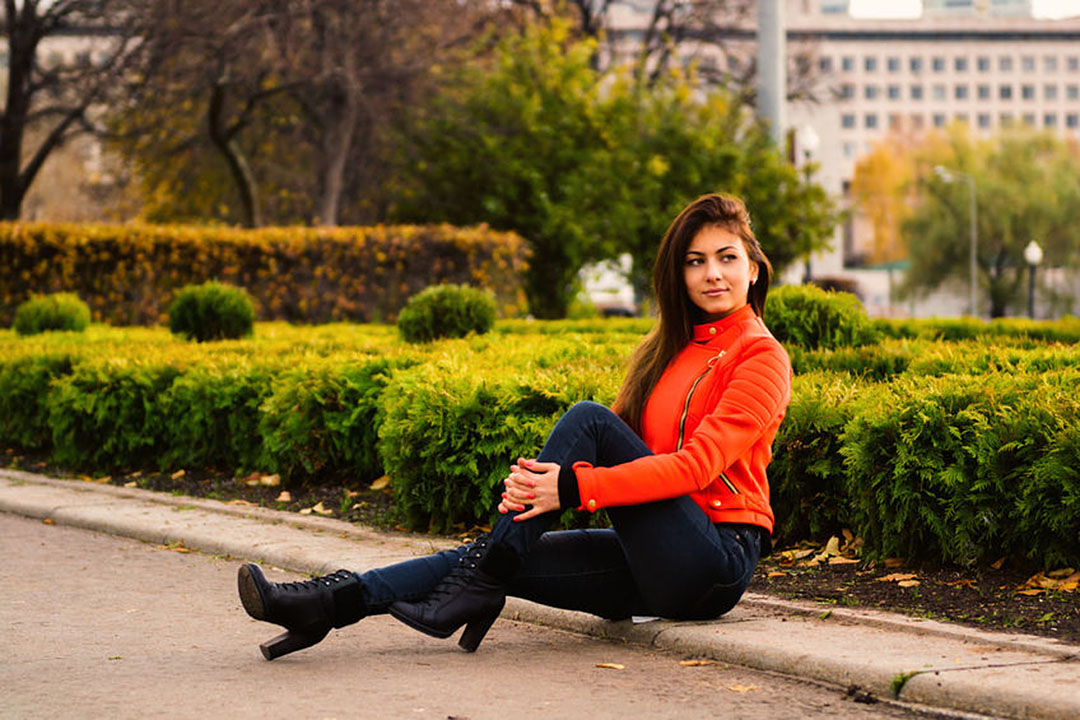 Young nice girl in vibrant orange jacket walking in autumn city