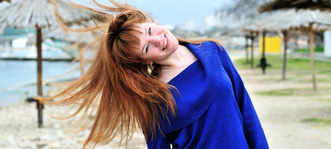 cute red-headed girl wearing bright blue sweater