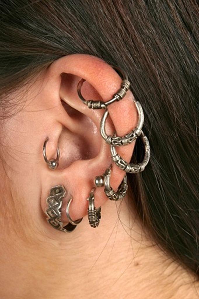woman ear multiple piercings multiple earrings enl