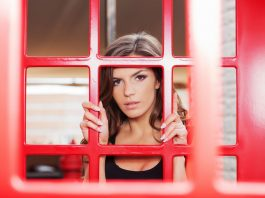 Beautiful young woman looking through the telephone booth