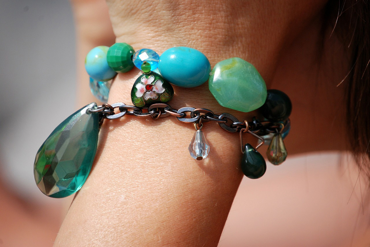 girl wearing charm bracelet with turquoise beads