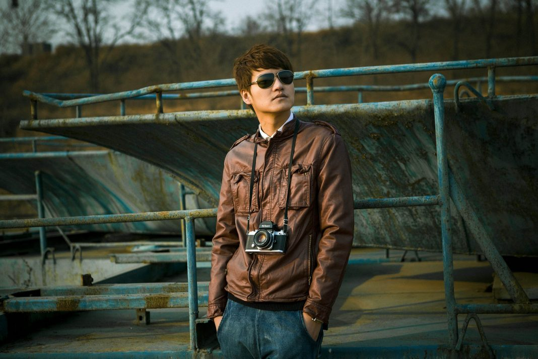 man in sunglasses jeans and brown jacket
