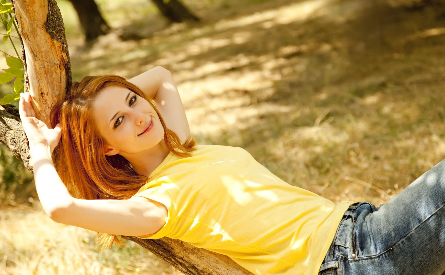 redhead wearing yellow t-shirt with blue jeans posing in tree