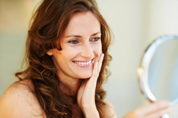 woman-looking-in-mirror-at-smile