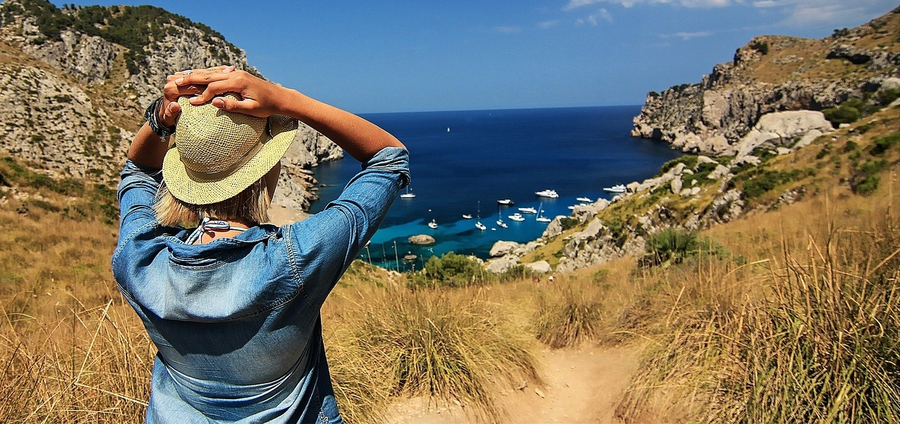 girl wearing denim jacket straw hat looking down at harbor from hill