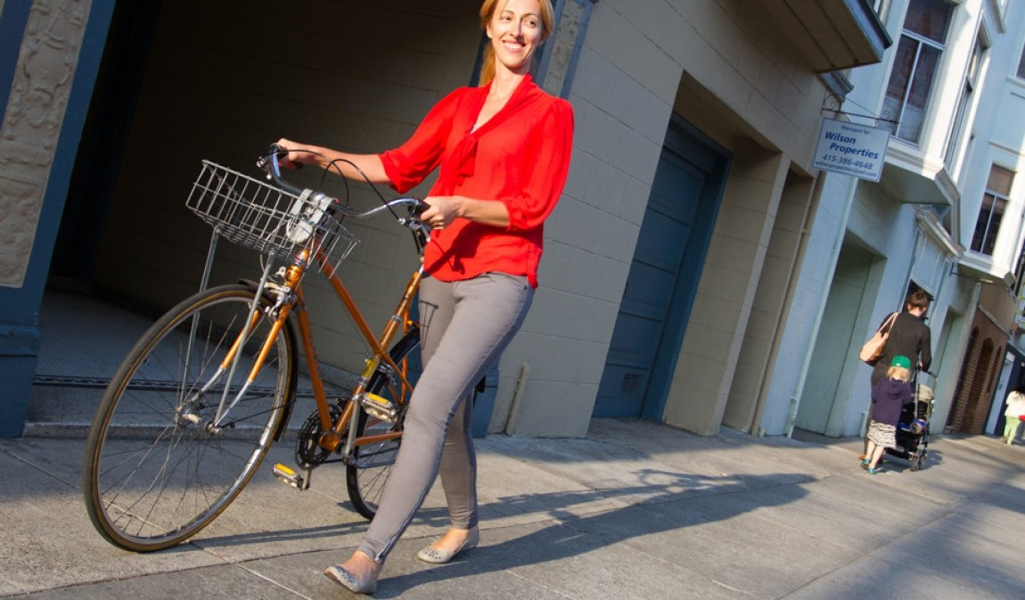woman wearing gray bike to work jeans betabrand with red top