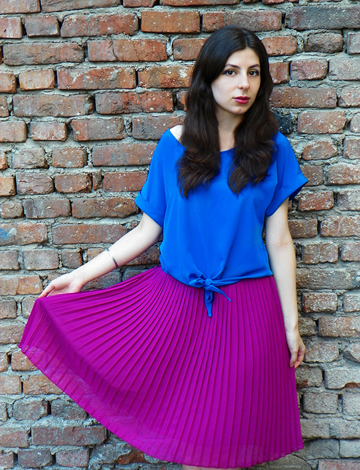 Blogger Laura Tenshi wears electric blue top with purple pleated skirt