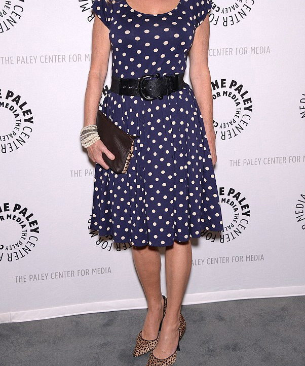 Chloe Webb wearing a navy blue white polka dots dress with a pair of leopard print