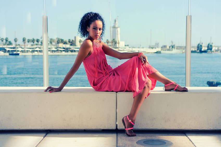 Portrait of a young black woman afro hairstyle wearing long pink dress in the harbour