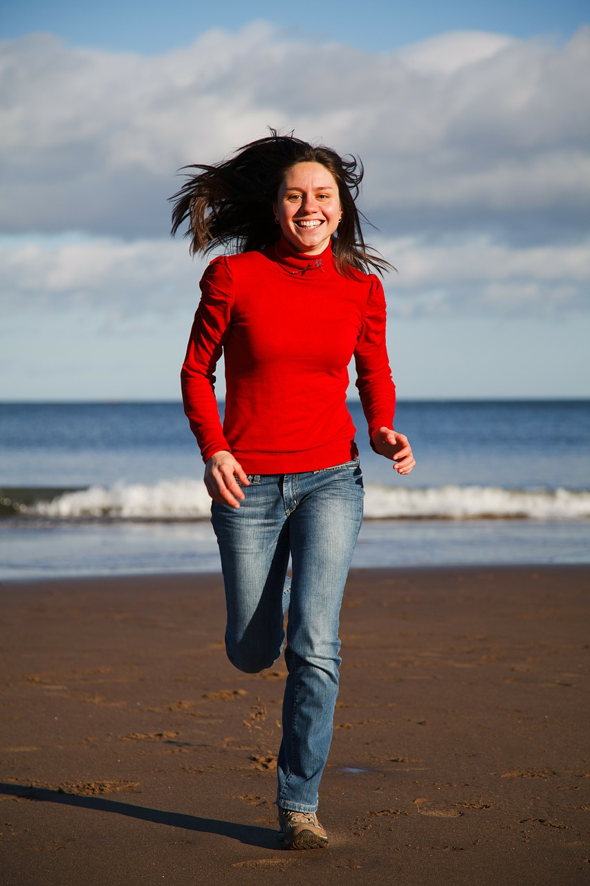 woman running on beach in jeans and sweater