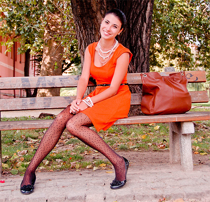 Fashion blogger Gabriela Jordan from the Czech Republic wears black flats with an orange dress